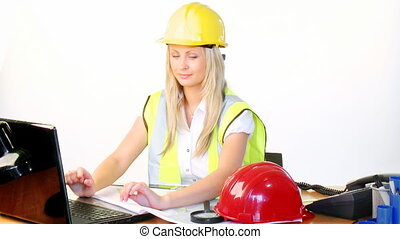 Female architect on phone and using a laptop