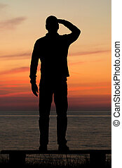 Looking at the sunset - Silhouette of male person against a...