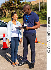 african student driver with instructor filling forms