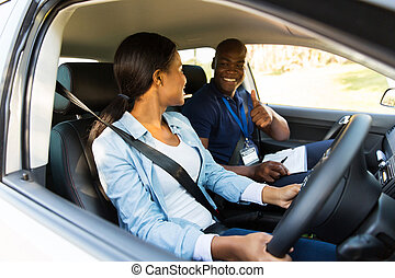 driving instructor giving thumbs up to learner driver