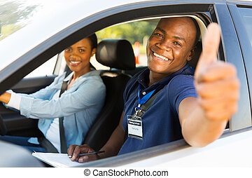 male african driving instructor giving thumb up