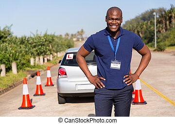 african driving instructor standing in testing ground -...
