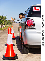 african student driver giving thumb up - cheerful african...
