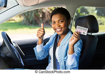 african girl holding her driver's license - cheerful african...