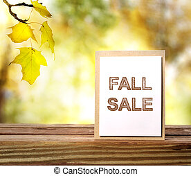 Fall Sale sign over yellow leaves background