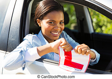 african girl sitting in a car tearing a L sign after having...