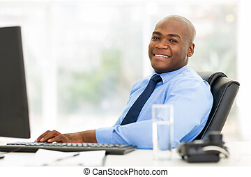 african businessman sitting in office looking at the camera...