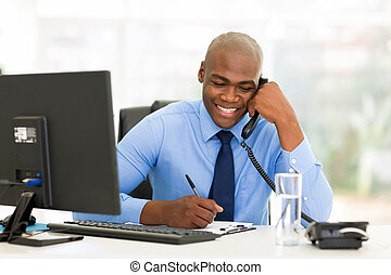 african businessman talking on landline phone - happy...
