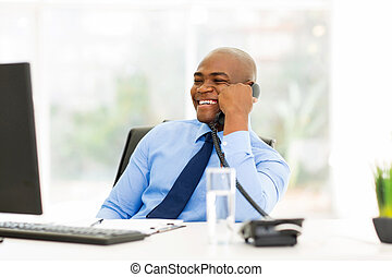 afro american businessman talking on landline phone -...