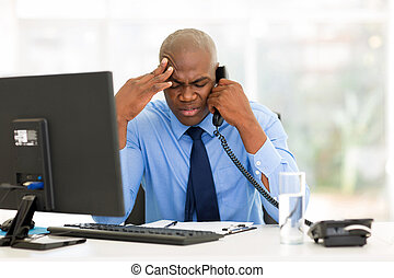 stressed businessman talking on landline phone in modern...