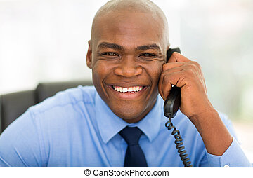 african businessman using landline phone - happy african...