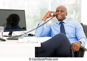 african american businessman using landline phone - handsome...