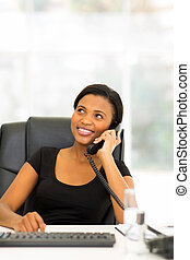 young african businesswoman using landline phone - beautiful...