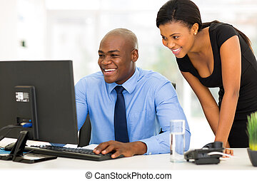 african secretary with her boss working on computer -...