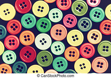 Sewing buttons on a dark background - Colorful sewing...
