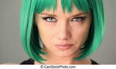 Green-eyed woman wearing a green wig - Close up of the eyes...