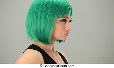 Thoughtful woman wearing a green wig staring sideways at the...