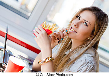 working lunch: close up image of drinking & eating fries beautiful young business woman blond girl having fun working on laptop pc computer in restaurant or coffee shop smiling & looking at camera
