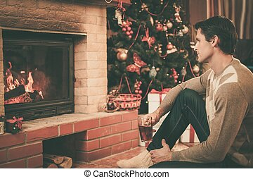 Man with cup of hot drink near fireplace in Christmas...