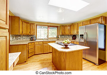 Golden tones kitchen interior with island and skylight
