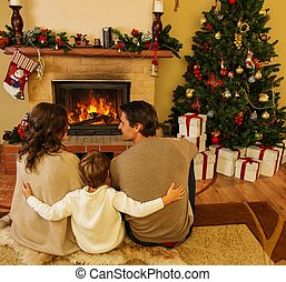 Family near fireplace in Christmas decorated house interior...