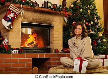 Young woman near fireplace in Christmas decorated house...