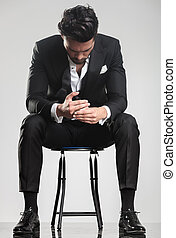 man in tuxedo looking down while sitting on a stool, -...