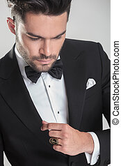 elegant young man in tuxedo looking down - Close up picture...