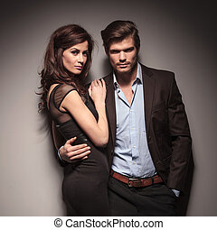 Fashion couple leaning on a dark grey wall looking into the...