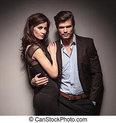 Fashion couple leaning on a dark grey wall
