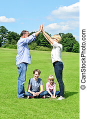 Family of four is having fun in the park - Parents playing...