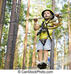 little cute boy in helmet runs track in forest