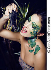 woman with creative make up like snake with rat in her...