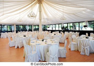 Wedding venue under a marquee with decorated tables and...