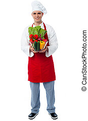 Chef holding glass bowl full of vegetables