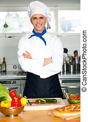 Male chef chopping vegetables in table - Young handsome male...