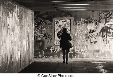 underpass - a woman goes through an underpass in the city of...