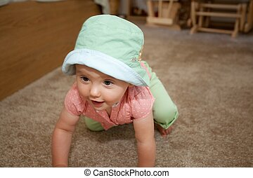 Green hat - Caucasian baby girl in green hat playing on a...