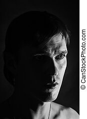 Black and white portrait of a young man on a black...