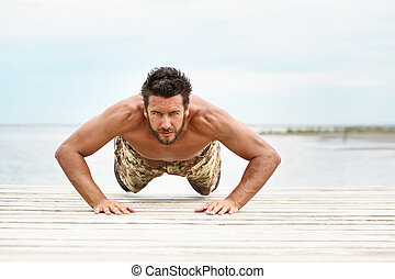 Fit shirtless male fitness model in push up exercise