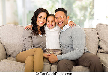 family sitting at home - happy family sitting on the couch...