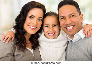 little girl hugging her parents - portrait of pretty little...