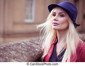 Stylish young blond woman waiting outdoors with her long...