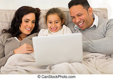 family using laptop computer at home - modern family using...