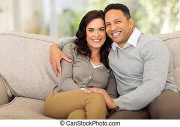 couple sitting on sofa at home - portrait of cute couple...
