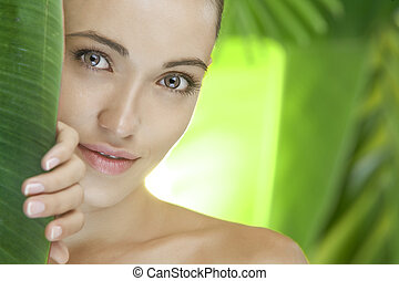 tropic face - portrait of young beautiful woman on green...