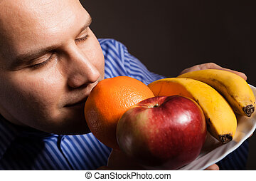 Diet nutrition. Happy young man smelling fruits. - Diet and...