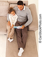 father reading a book to his daughter - top view of father...