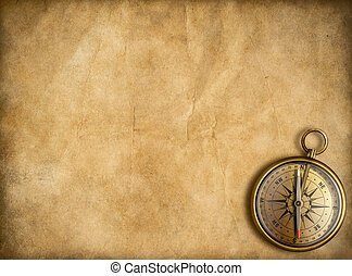 old brass or golden compass with vintage map background -...