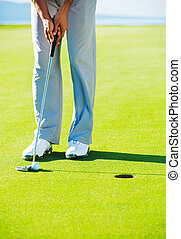 Golfer on Putting Green Hitting Golf Ball into the Hole